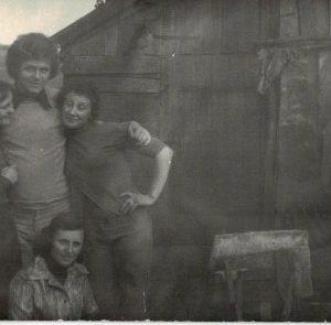 Młodzież na tle drewnianych obórek.