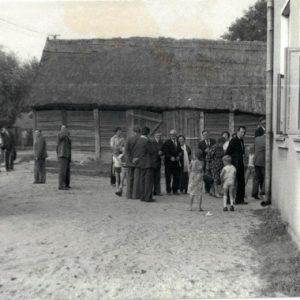 Goście weselni przed remizą. W tle drewniana stodoła Szymankiewiczów koło remizy a przed nią stał kierat - maszyna do cięcia słomy napędzana siłą konia